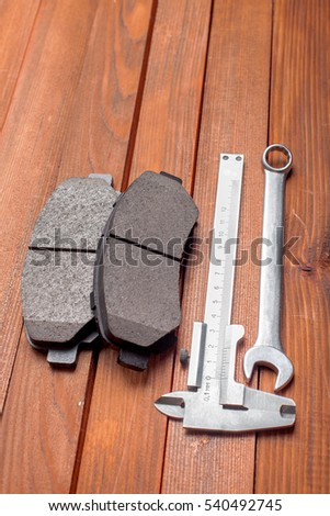 The tool for replacement of brake pads: a spanner wrench, a caliper and spare parts for the car on a wooden background from boards.