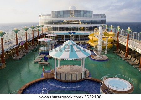 The top deck of a cruise ship with water slides, hot tubs, pool, and other items - stock photo