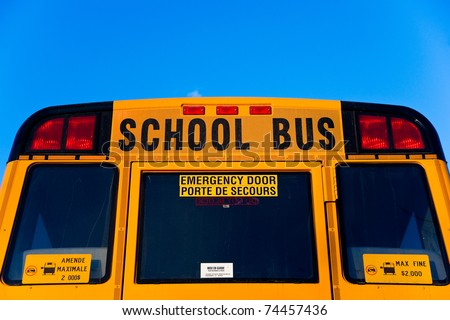 """The top half of the back of a yellow School Bus displaying the words """"School Bus"""" and """"emergency door"""". - stock photo"""
