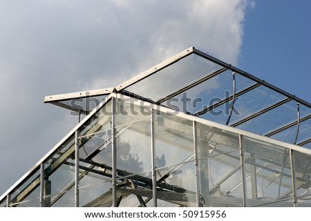 The Top Of A Modern Greenhouse, With Its Glass Panels Open To Let In Fresh