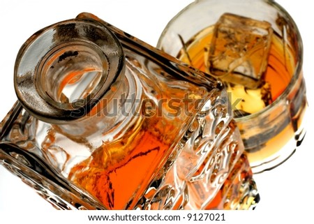 The top of an open ornate whiskey decanter and a glass of liquor and ice. - stock photo