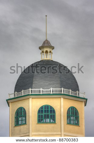 The top of the dome cinema building in Worthing, England. This is a famous 1930's building on the seafront.  The building is yellow with green windows and has a white railing and grey domed roof. - stock photo
