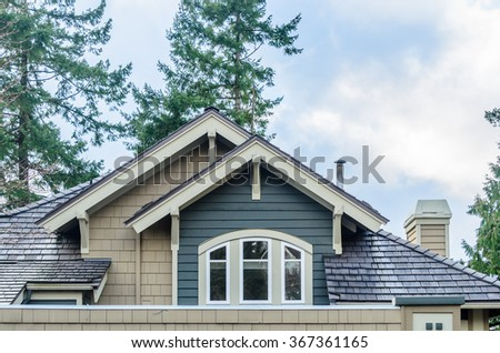 The top of the house or apartment building with nice window. - stock photo