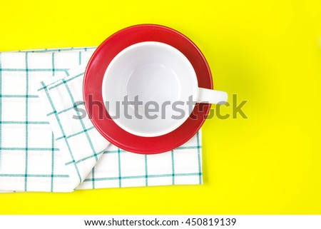 the top view of empty white coffee or tea cup with red dish and towel on vibrant color background - stock photo