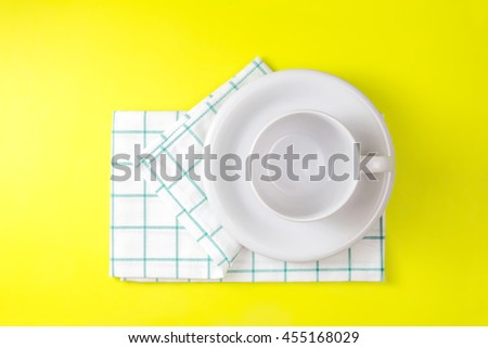 the top view of empty white coffee or tea cup with towel on vibrant color background - stock photo