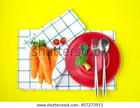 the top view of fresh broccoli a, carrots and tomato with red dish and towel on vibrant color background , healthy food concept - stock photo