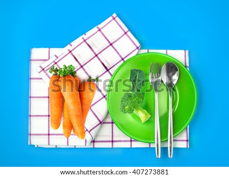 the top view of fresh broccoli and carrots in green dish and towel on vibrant color background , healthy food concept - stock photo