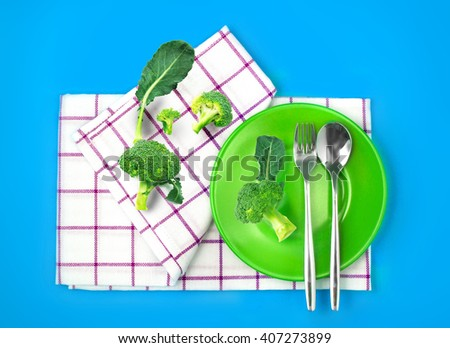 the top view of fresh broccoli in green dish and towel on vibrant color background , healthy food concept - stock photo