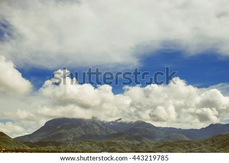 The tops of mountains under the beautiful volume clouds.