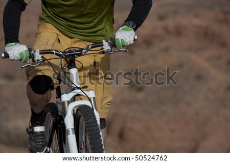The torso of a man riding a mountain bike in a desert landscape. Horizontal shot. - stock photo
