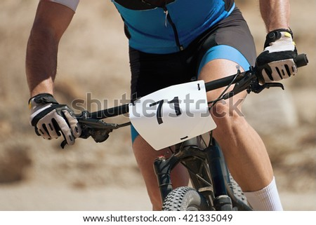 The torso of a man riding a mountain bike in the race