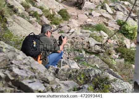 The tourist is taking a photograph on the slope of the mountain in Corsica.