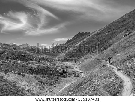 The tourist on the moraine of the glacier Gokyo in the area of the Cho Oyu (8153 m) - Nepal, Himalayas (black and white) - stock photo