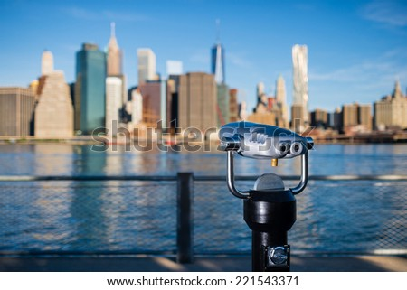 The tourist telescope with blurred New York City silhouette in the background - stock photo