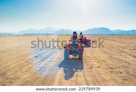 The tourists ride on quads through the Sahara desert to the Bedouin village, Egypt. - stock photo