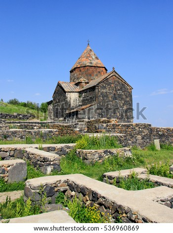 The tourists visit Sevanavank Monastery, located on Sevan Peninsula, among the bright green hills