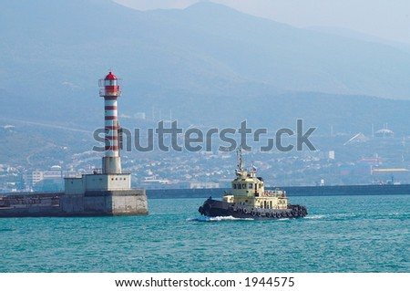 The towboat pass by a beacon on the end of a pier - stock photo