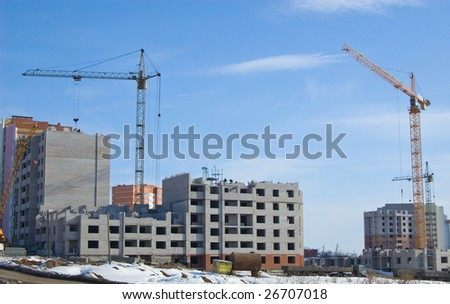 The tower cranes on building of the high-rise house against the blue sky