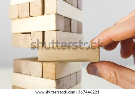 The tower from  wooden blocks and man's hand take one block - stock photo