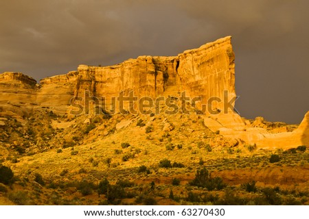 The Tower of Babel glows in early morning light as rainstorm clouds pass in the background in Arches National Park. - stock photo