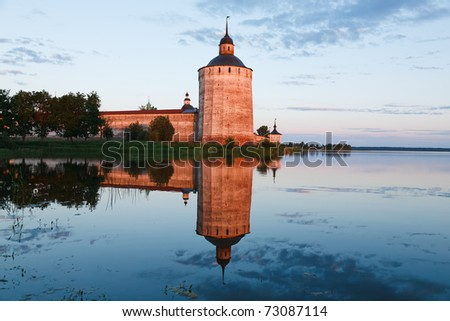 The tower of old monastery is reflected in a sunset in lake - stock photo