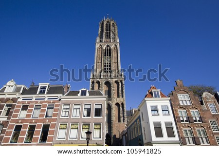 The tower of the Dom cathedral above a row of historical houses of Utrecht, Holland - stock photo