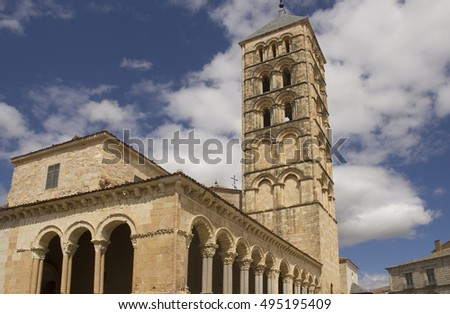The tower of the San Esteban Church against a clouds in a blue sky in Segovia, Spain