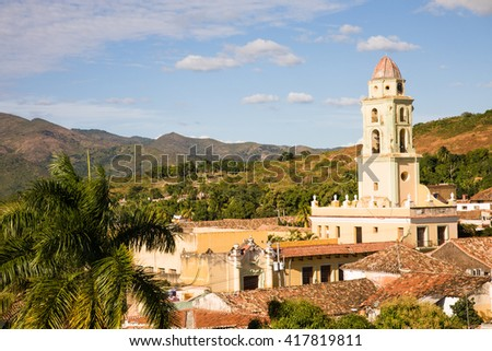 The tower of the San Francisco Convent in the historic center of the colonial city of Trinidad, Cuba with view on surrounding hills - stock photo