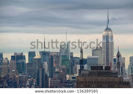 The towers and spires of Midtown Manhattan rise in front of a stormy sky - stock photo