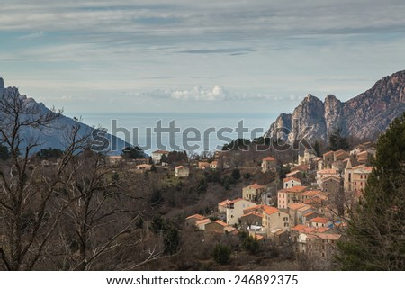 The town of Evisa in Corsica with mountains and the Mediterranean sea behind - stock photo