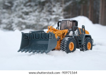 The toy heavy bulldozer of yellow color on the snow - stock photo