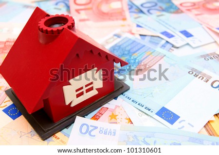 The toy house and money. - stock photo