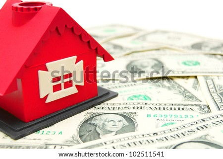 The toy house on money. On a white background. - stock photo