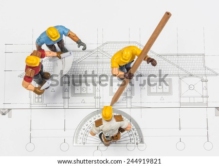 The toy model workers in construction on architectural blueprint - stock photo