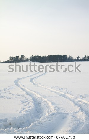 The traces left on snow from the lorry (on a sunset, traces pass through a field, instead of through road) - stock photo