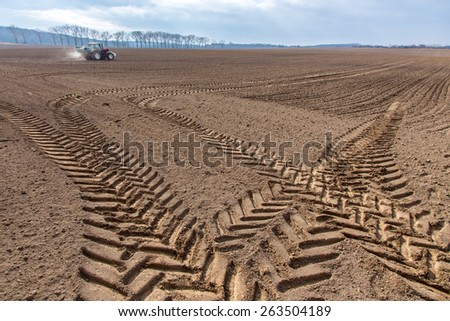The traces of the tractor working on the large field - stock photo