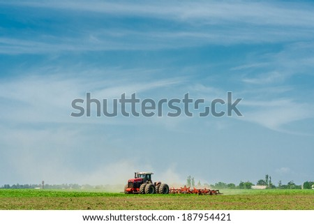 The tractor in the field on the background of blue sky - stock photo