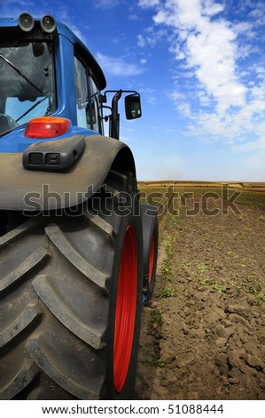The Tractor - modern farm equipment in field - stock photo