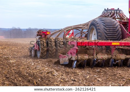 The tractor working on the large field - stock photo