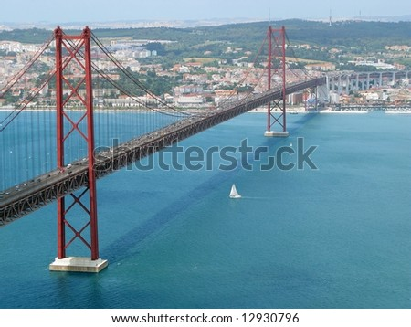 The traditional bridge over the river tagus (tejo), with a sailboat passing bellow. Lisbon, Portugal - stock photo