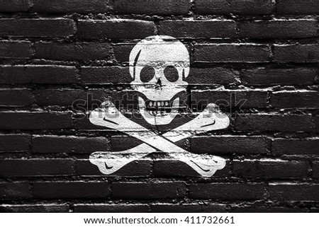 The traditional Jolly Roger of piracy Flag, painted on brick wall - stock photo