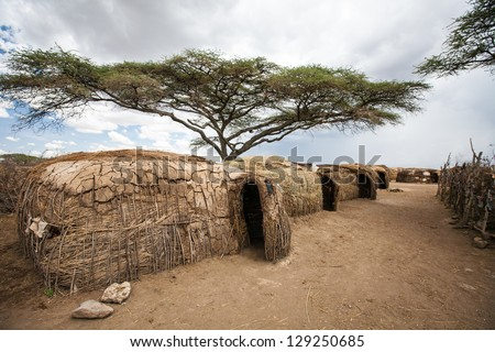 The traditional living space of the Masai people. Grass and mud huts surrounded by goat and cattle pens. Serengeti National Park, Tanzania - stock photo