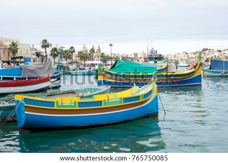 The traditional maltese luzzu boats in the harbor of fishing village Marsaxlokk in Malta