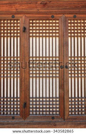 The traditional(old, vintage) wood(wooden) door of palace with old paper in korean(asian, chinese, japanese, korea, japan, china) heritage at the 15 century Chosun. - stock photo