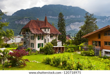The traditional, wooden, swiss houses with a garden against mountains - stock photo