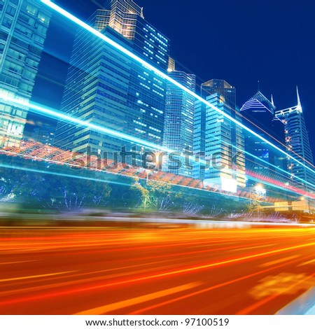 The traffic light trails in the street by modern building - stock photo