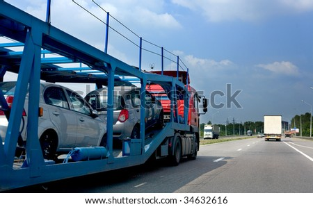 The trailer transports cars on highway - stock photo