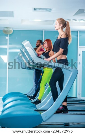 The treadmill in the gym. Sport and slender girl running on a treadmill. Athlete dressed in sports uniforms and running in the gym. - stock photo