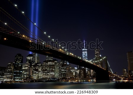 The Tribute in Light with Brooklyn bridge in New York City.  View from Dumbo, Brooklyn. Focus on bridge. - stock photo