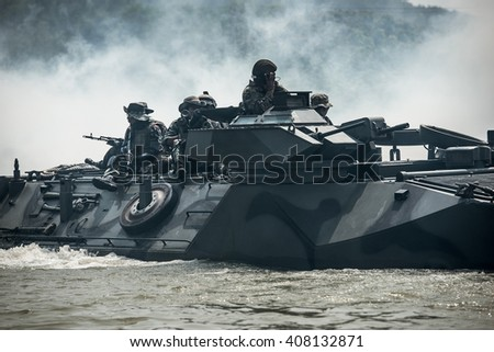 The troops conceal behind the smoke on the tank. - stock photo